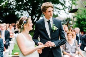 Brautpaar steckt sich die Ringe an im Garten
