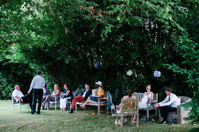 Hochzeitsgäste sitzen unter Baum