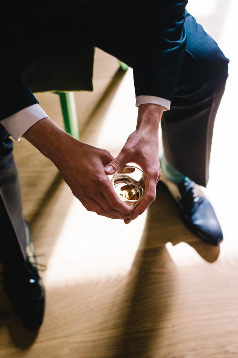 Bräutigam hält ein Glas Whiskey in der Hand