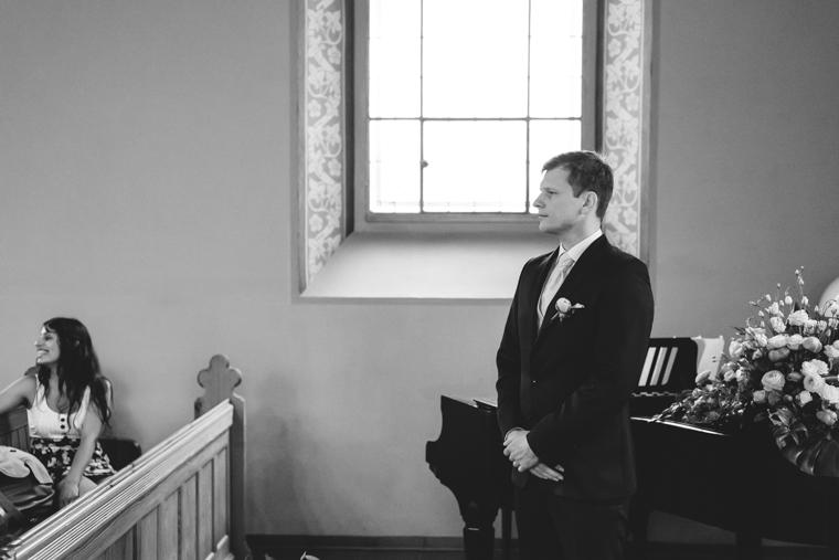 Bräutigam wartet neben Altar in Waldkapelle auf seine Braut