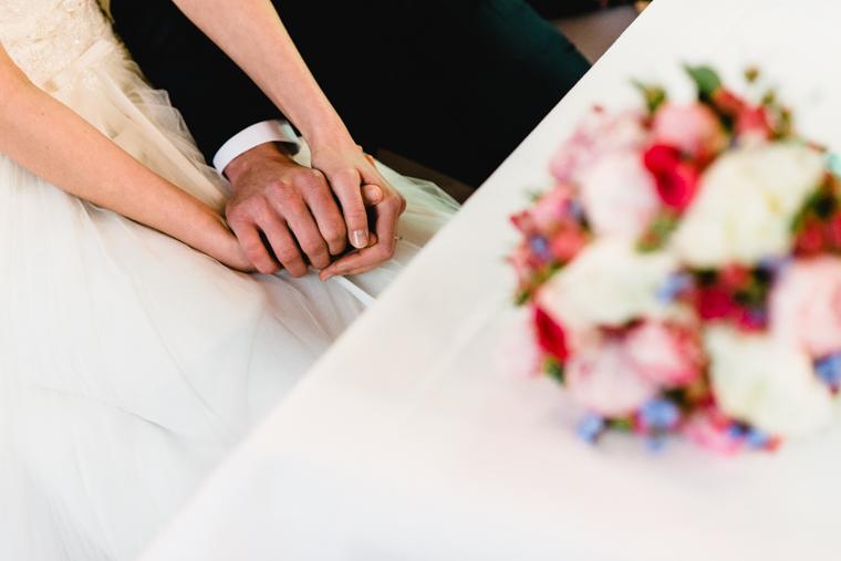 Brautpaar beim Händehalten mit Brautstrauss im Vordergrund