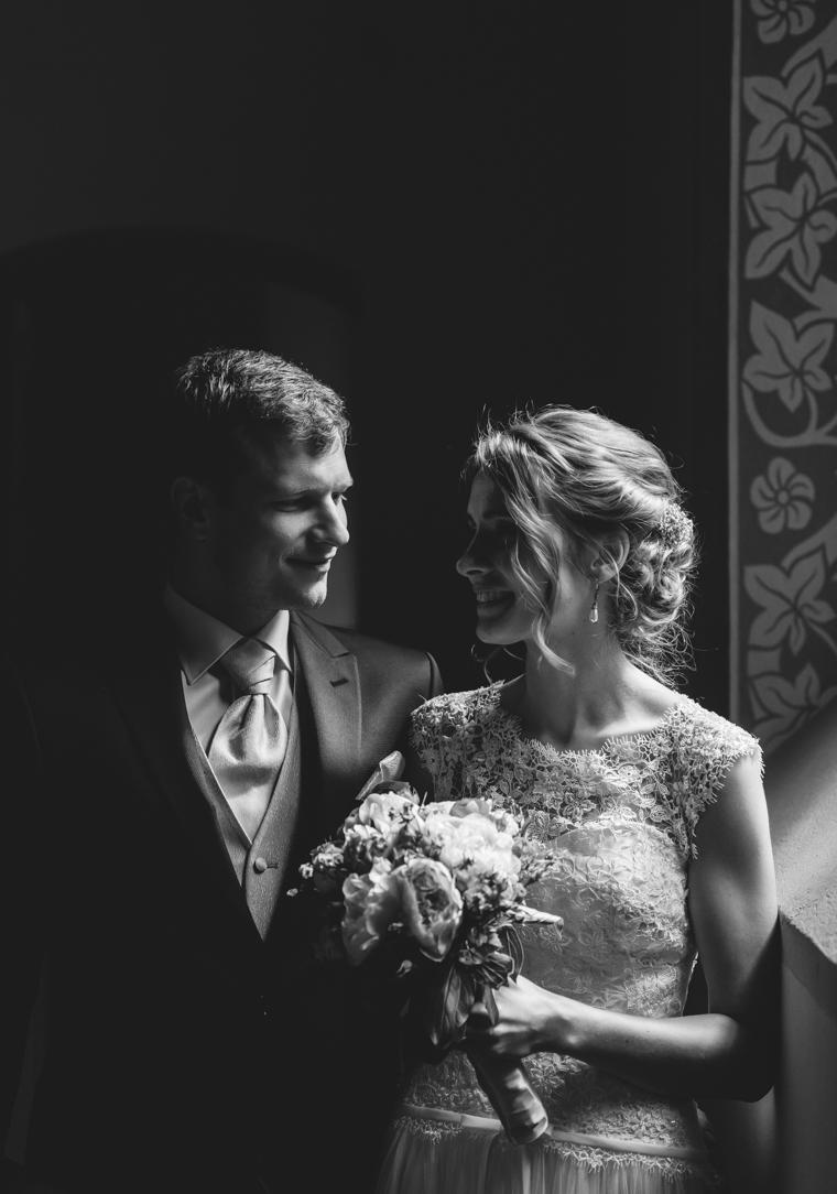 Gutaussehendes Brautpaar in natürlichem Licht neben Fenster in Waldkapelle Bad Belzig