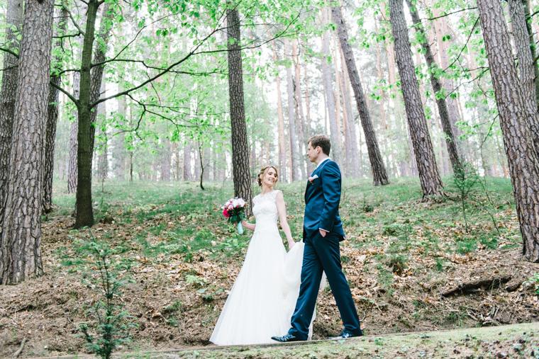 Braut und Bräutigam schlendern durch Nadelwald