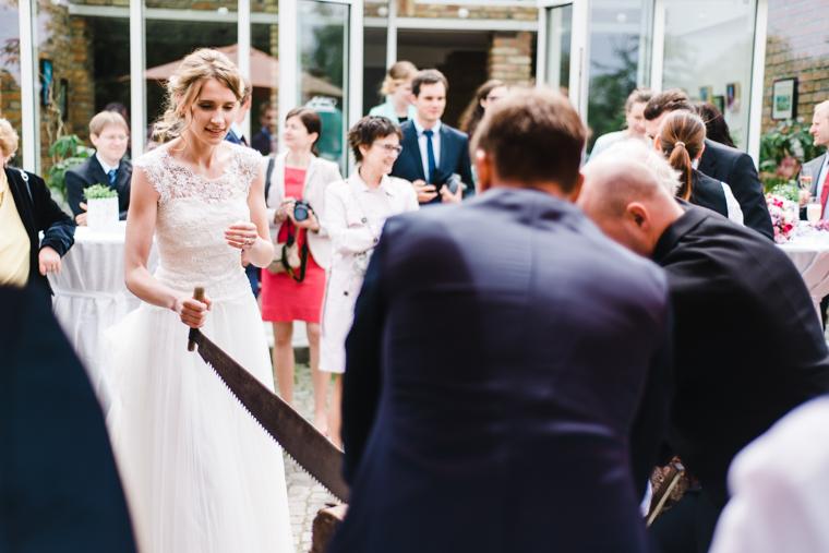 Hochzeitsbrauch Braut und Bräutigam sägen Baumstamm