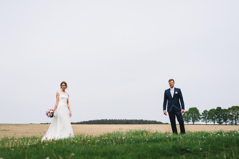 Brautpaar steht in weiter Landschaft in Brandenburg