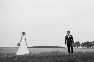 Braut und Bräutigam stehen auf einem Feld in Brandenburg