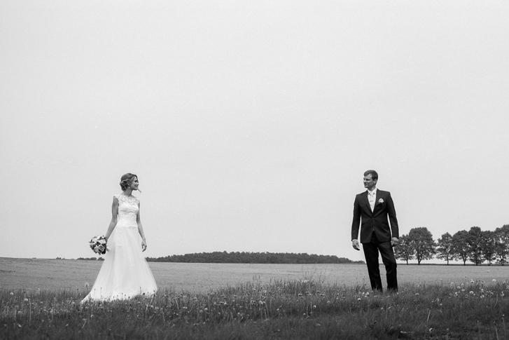 Hochzeitsfoto in Schwarz Weiß Paar steht auf Feld