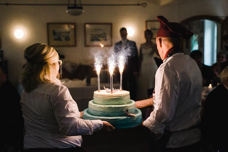 Hochzeitstorte mit brennenden Kerzen wird hereingetragen