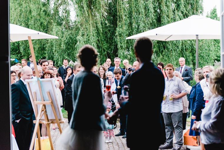 Aufnahme des Hochzeitspaares von hinten wie sie auf ihre Gäste schauen