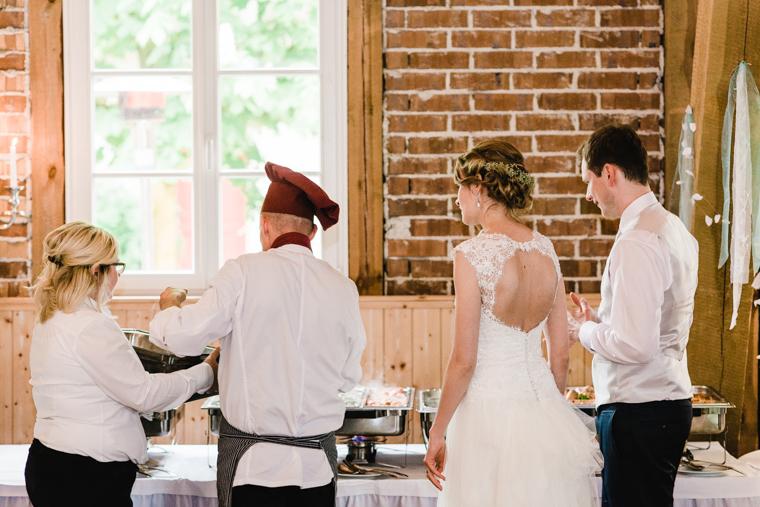 Brautpaar steht mit Koch vor dem Hochzeitsbuffet