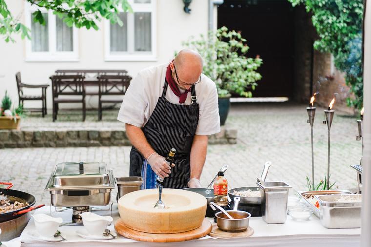 Koch bereitet Pasta in Parmesan zu