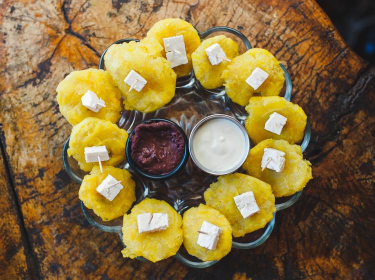 Tostones - Frittierte Bananenscheiben mit Käse und saurer Sahne sowie Bohnenpuree als Dips.