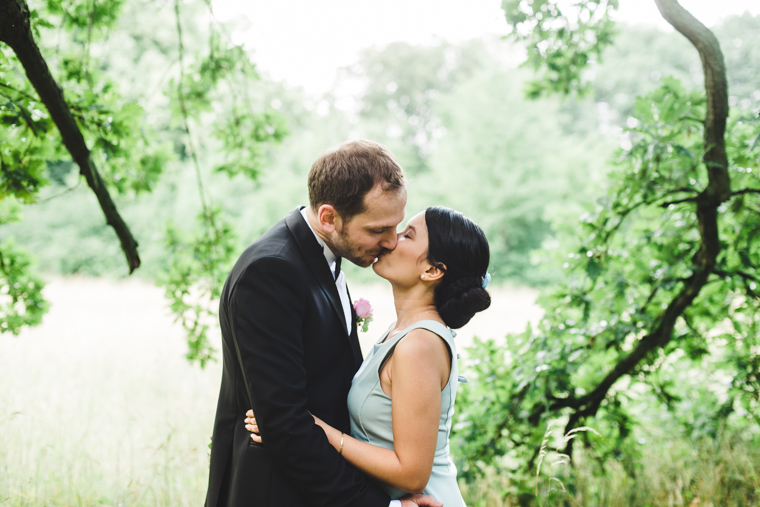 Beautiful wedding couple kissing under a tree