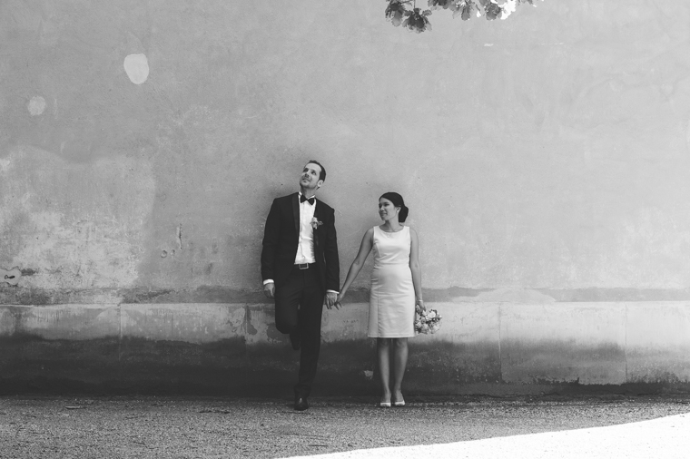Bride and groom in front of wall