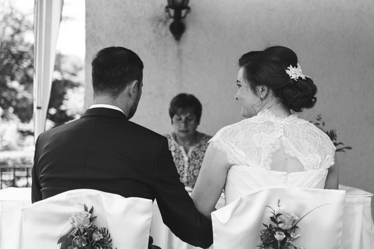 Foto eines sich in die Augen schauenden Hochzeitspaares von hinten