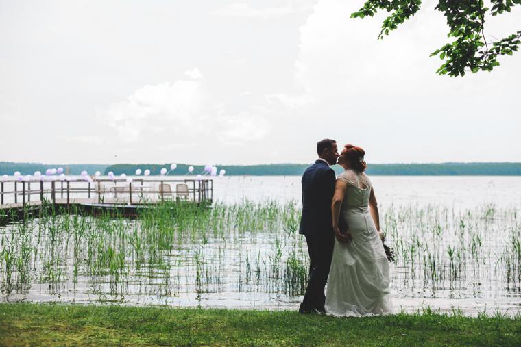 Braut steht küssend am Ufer eines Sees