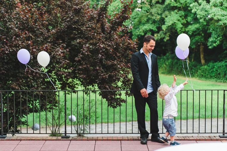 Vater und Kind auf Terrasse mit Luftballons
