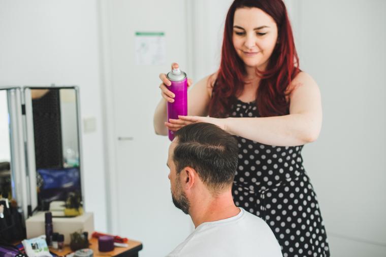 Stylistin stylt Haare eines Bräutigams