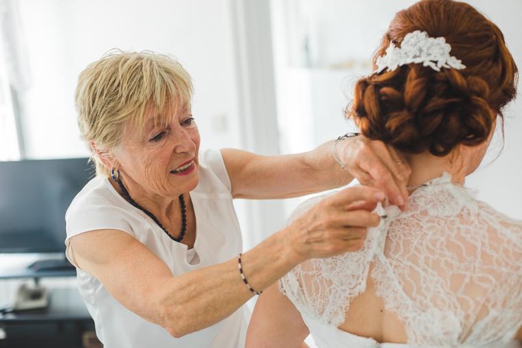 Mutter hilft Braut beim Anziehen des Brautkleids