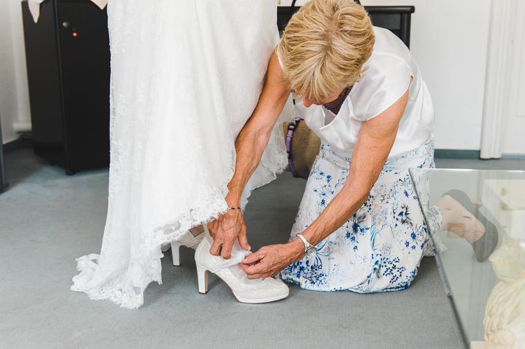 Mutter hilft Braut beim Anziehen der Schuhe