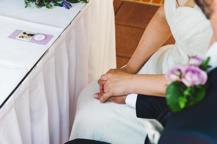 Brautpaar hält Hände während Trauung