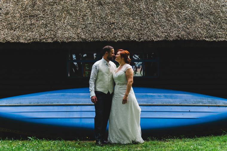 Hochzeitspaar steht vor Boot