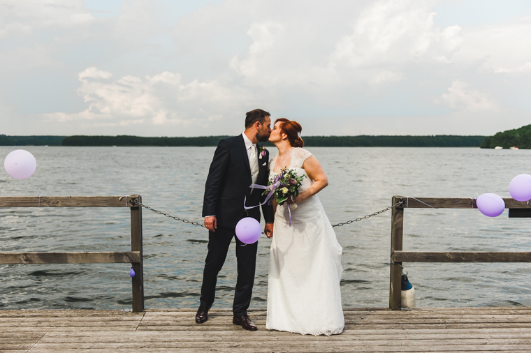 Brautpaar steht auf einem Steg und küsst sich