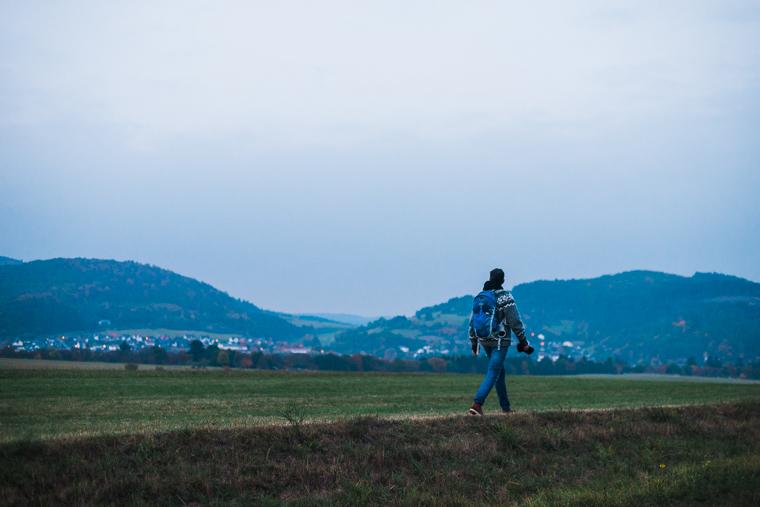 Willi Weitzel geht in der Dämmerung auf einem Feld an einem Dorf vorbei