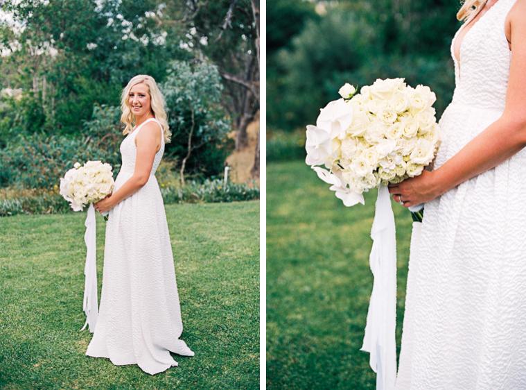 Schöne Braut mit Brautstrauss steht auf Wiese