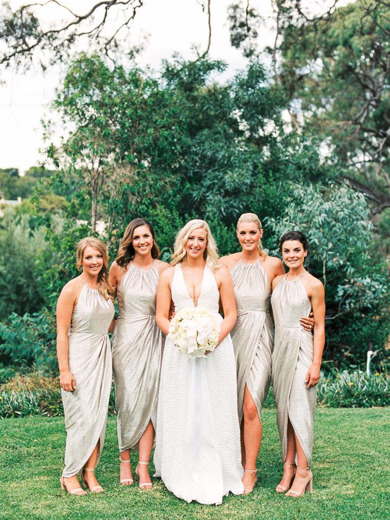 Braut und ihre besten Freundinnen lachen in die Kamera