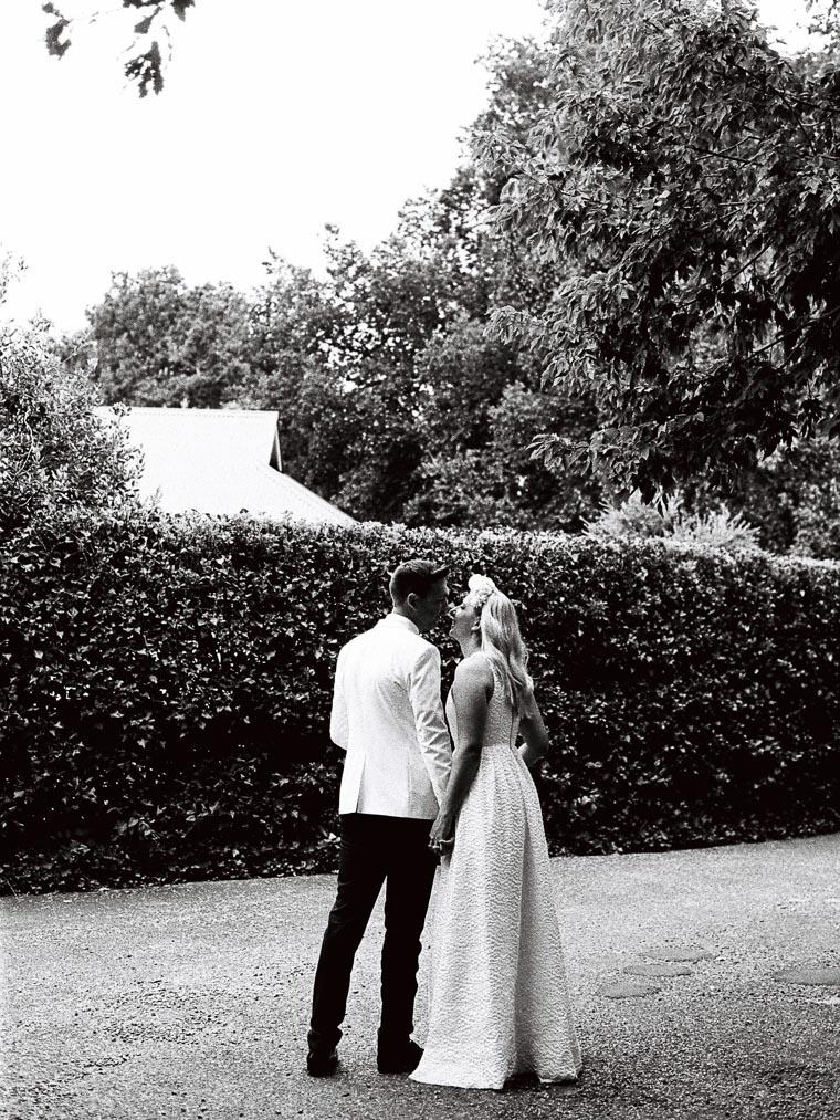 Küssendes Hochzeitspaar fotografiert auf Schwarz Weiß Film