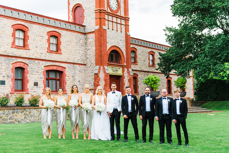 group shot bridal party in front of old winery building
