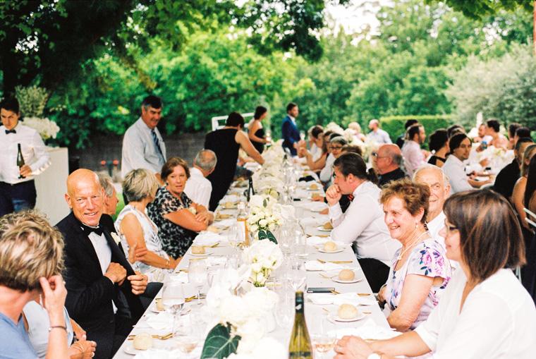 Gäste sitzen an Tischen und trinken Champagner