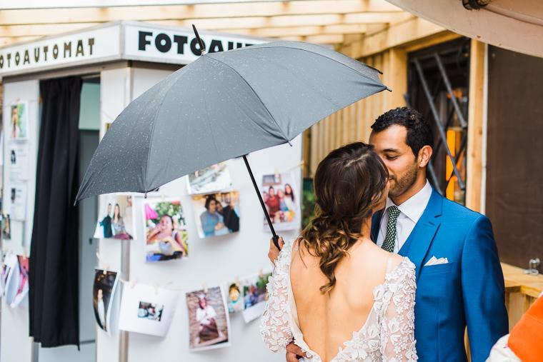 brautpaar küsst sich unter regenschirm