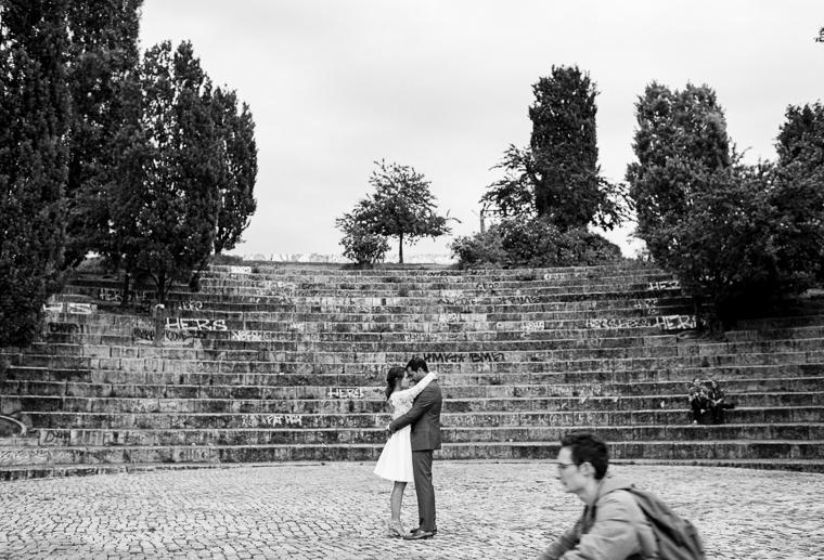 französisches paar mit küsst sich im mauerpark mit vorbeifahrendem radfahrer im vordergrund