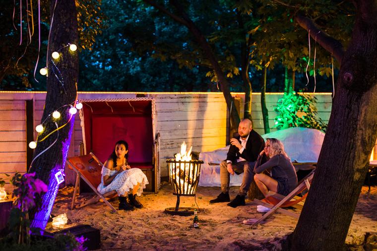 hochzeitsgäste sitzen um lagerfeuer in der stadt