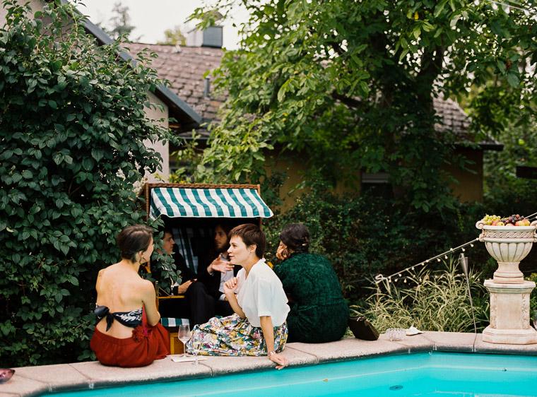 Freunde sitzen während Hochzeit am Pool