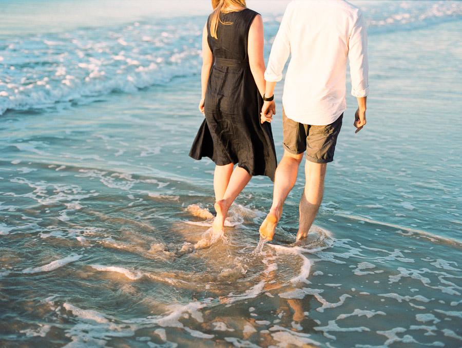 Verlobte und Verlobter laufen durch Wellen