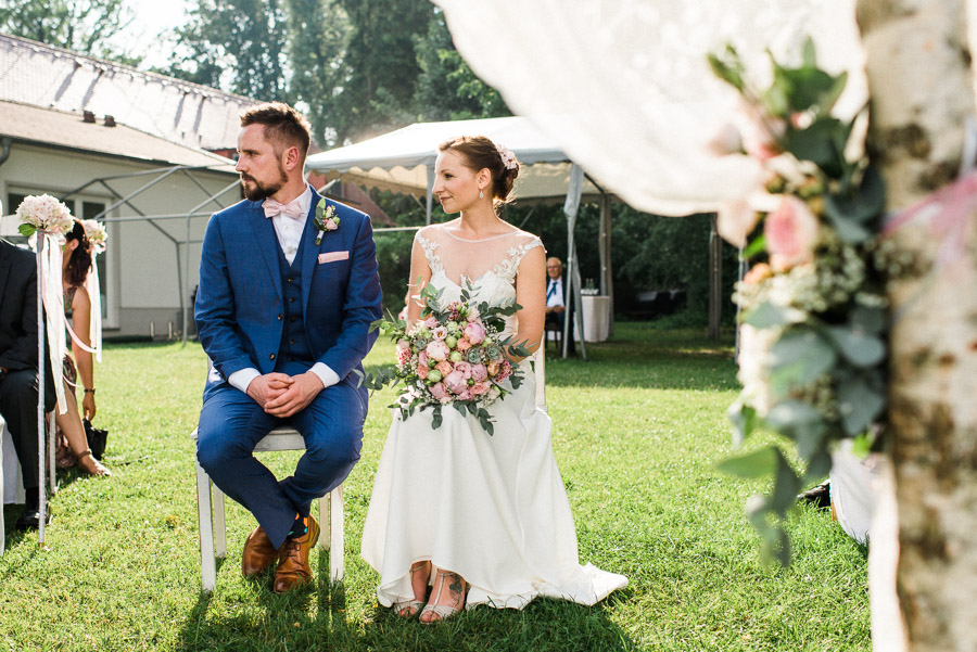 bride and groom sitting next to each other during ceremony