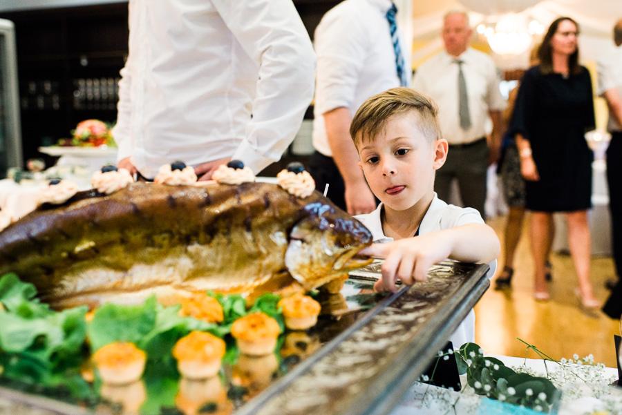 Kind spielt mit Essen am Hochzeitsbuffet