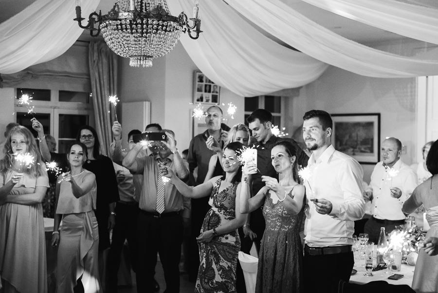 Gäste halten Wunderkerzen während Hochzeitstanz