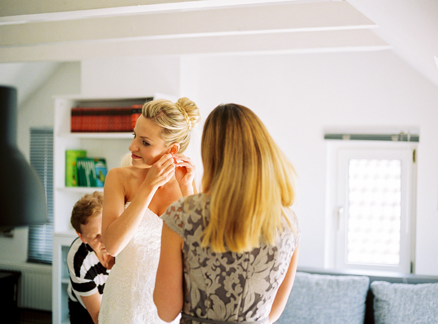 Braut steckt sich Ohrringe an