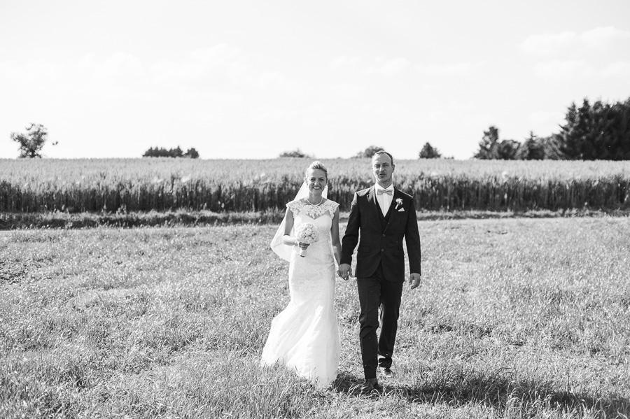 Braut und Bräutigam schlendern über Feld