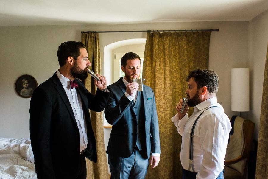 Bräutigam und Trauzeugen trinken Schnaps am Hochzeitsmorgen