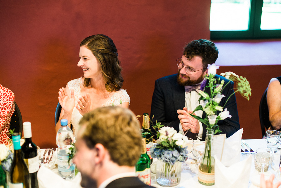 Bride and groom smile during wedding speech