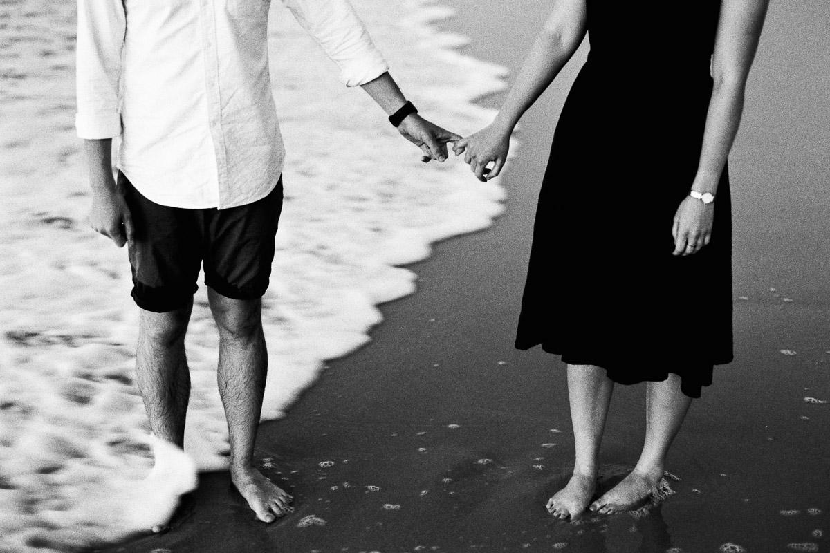 Hände haltendes Paar am Strand