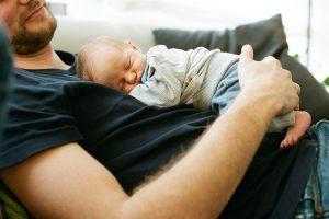 Baby liegt auf Bauch des Vaters