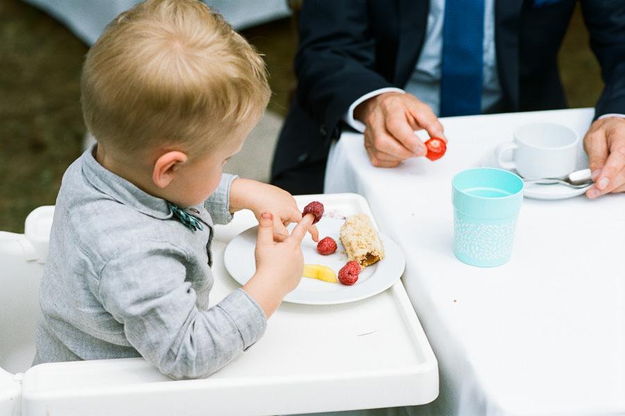 Kleinkind spielt mit Himbeeren