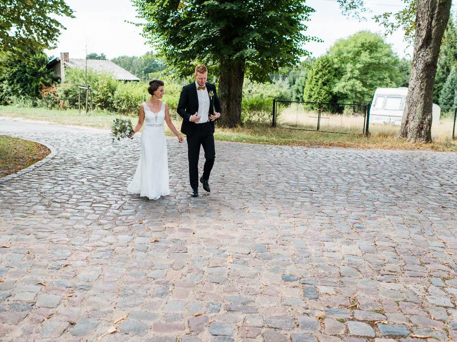 Hochzeitspaar läuft auf Allee