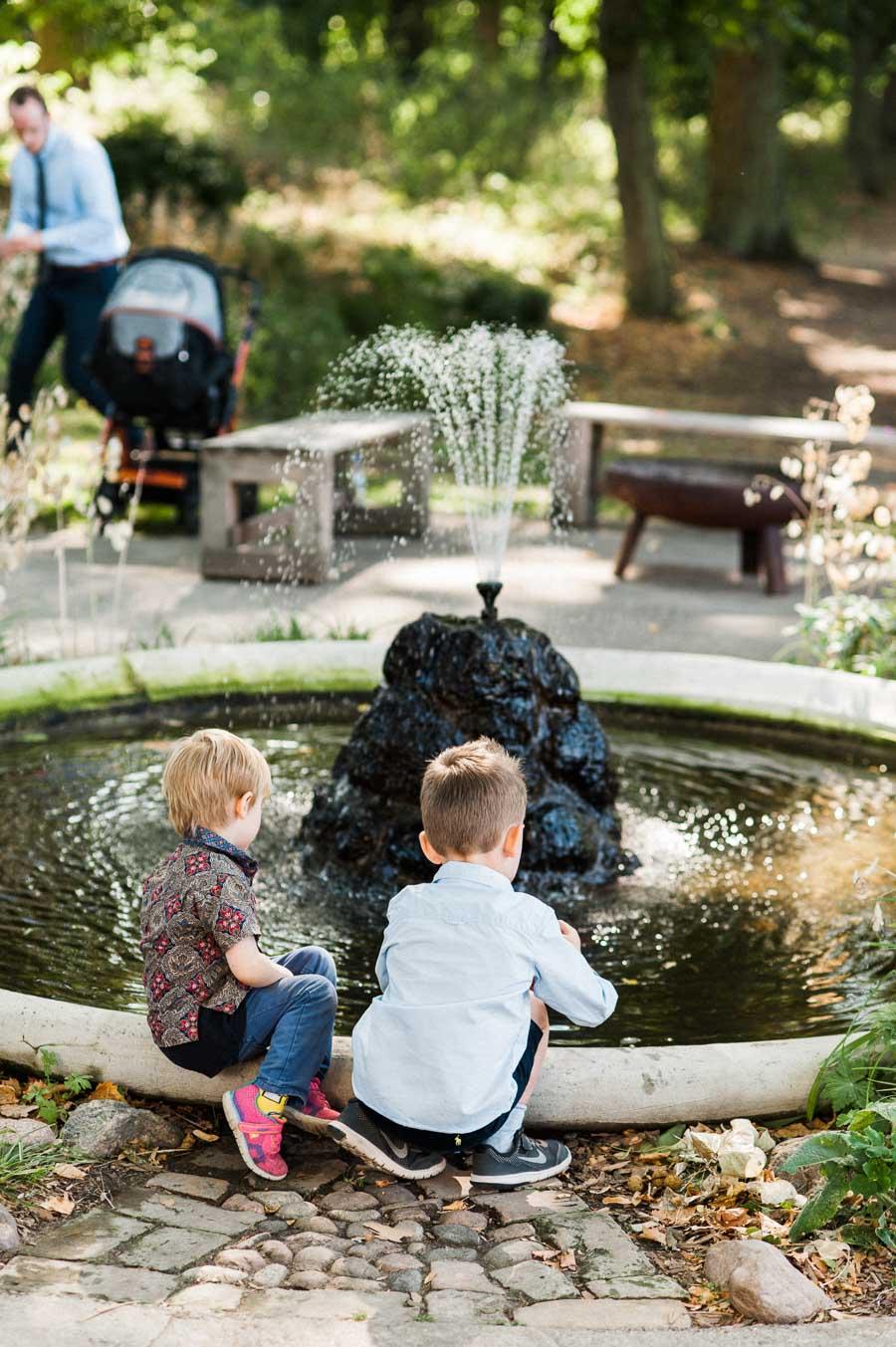 Kinder spielen am Springbrunnen